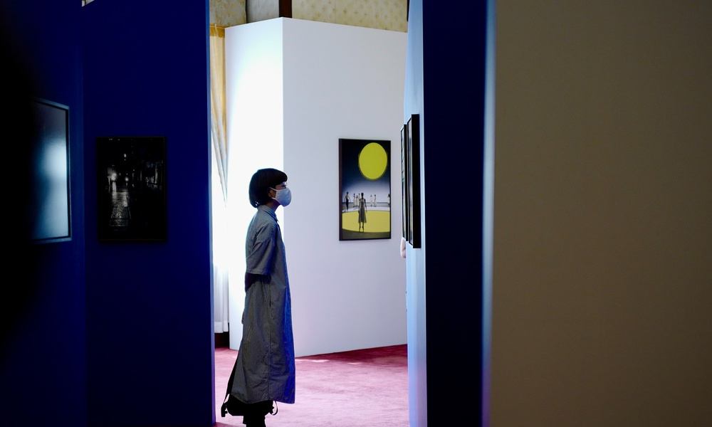 Spectator looking at a painting in colorful art exhibit